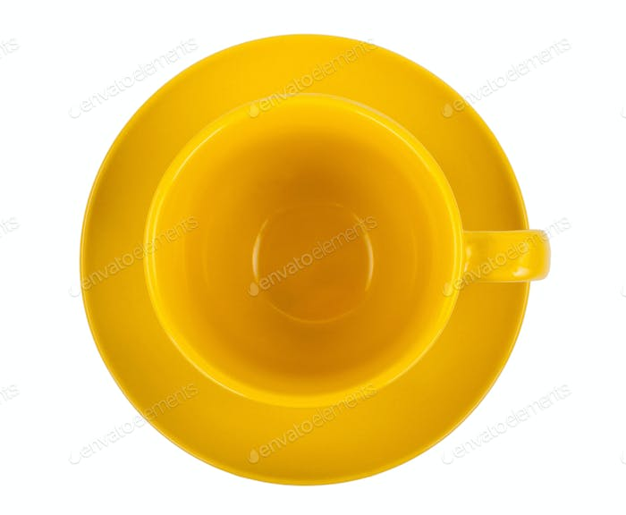 Yellow round empty tea cup on a saucer