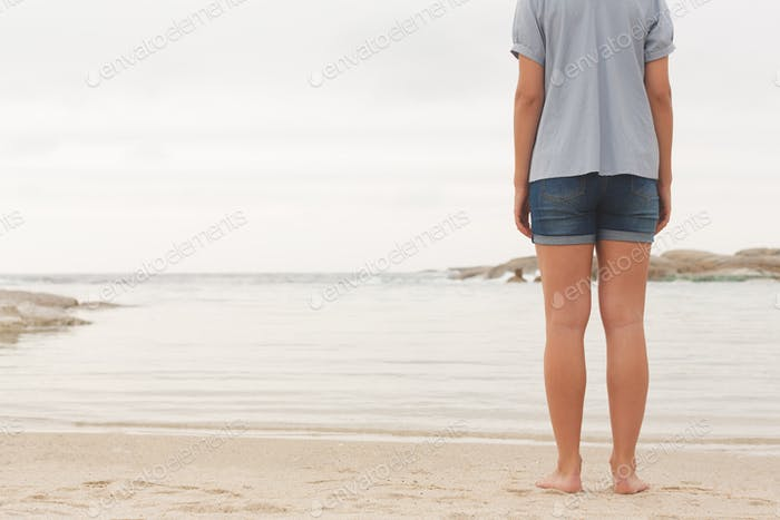 Low section of young Caucasian woman standing at beach on the sand. She is looking the sea