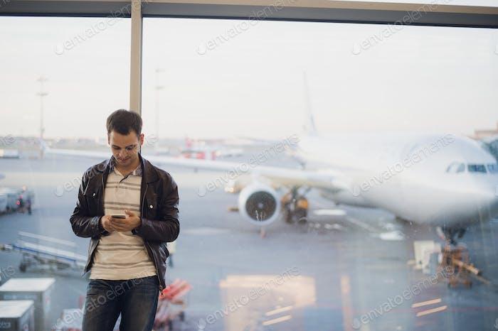 Hombre Negocios joven en el aeropuerto Uso teléfono inteligente.