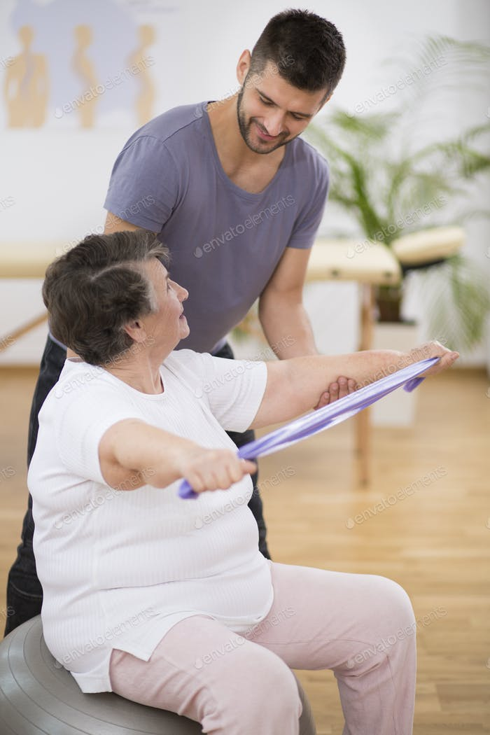 Elderly pensioner exercising with resistance bands with her professional physiotherapist