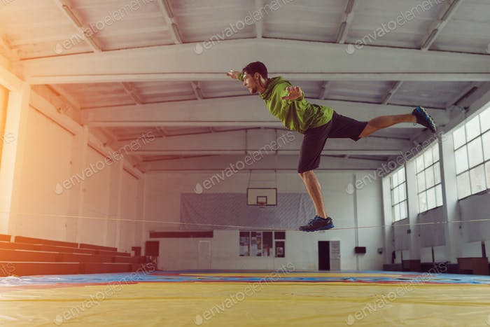Man slacklining walking and balancing on a rope, slackline in a sports hall