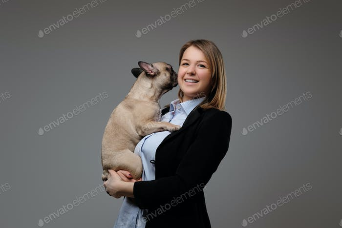 Portrait of a happy blonde woman breeder holds her cute pug. Isolated on gray background.