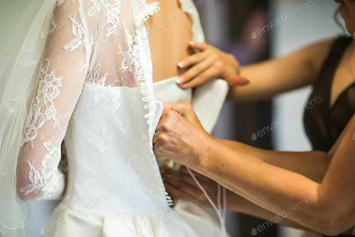 Brides maid helps bride  in wedding dress