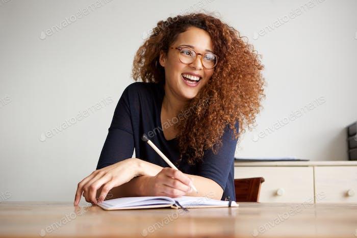 glückliche weibliche College-Studentin sitzen am Schreibtisch schreiben im Buch