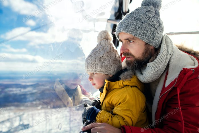 Father with small son inside a cable car cabin, holiday in snowy winter nature
