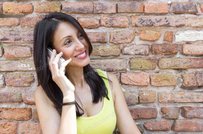 Woman talking on the phone and smiling outdoors.