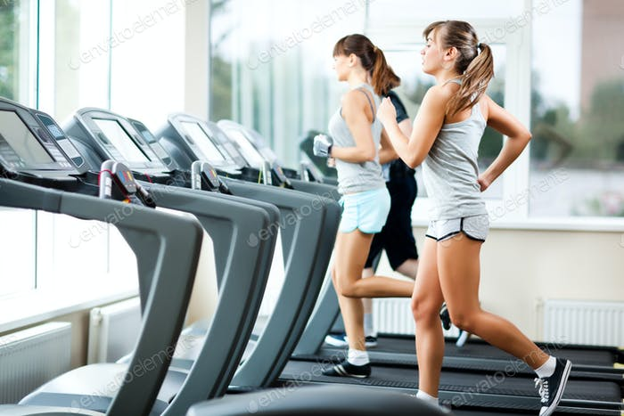 Two young beautiful slim women in sportswear running on treadmills in gym