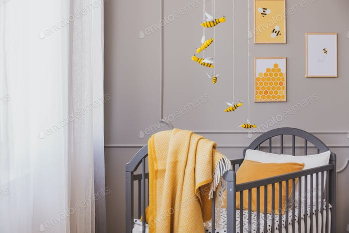Yellow blanket on grey wooden crib in bright baby bedroom with y