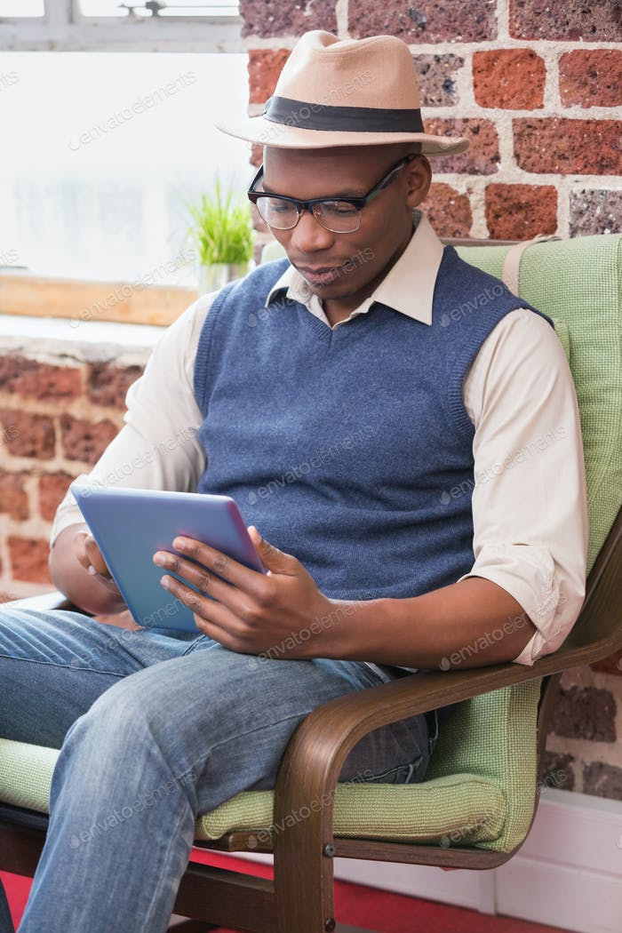 Concentrated young man using digital tablet