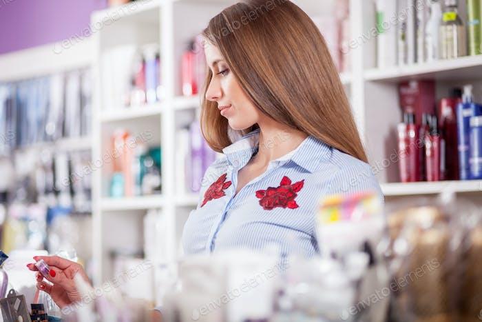 Kundenfrau wählt Kosmetik im Beauty-Shop