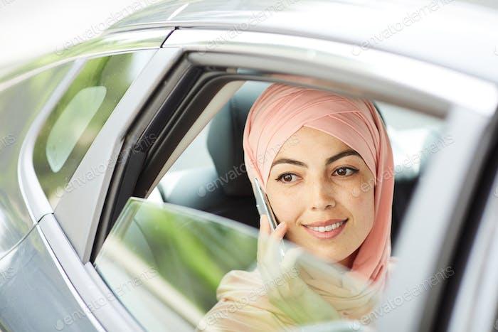 Pensive Muslim woman talking on phone in taxi