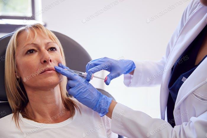 Reifen Frau sitzen in Stuhl sein geben botox Injektion durch weiblich Arzt