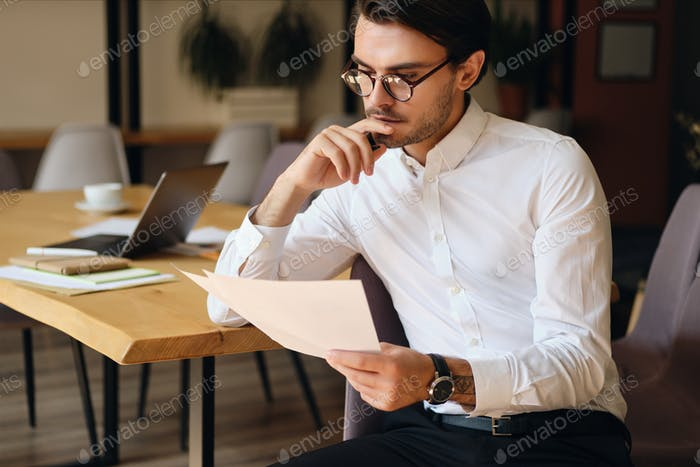 Young serious businessman in eyeglasses thoughtfully reading papers working in office
