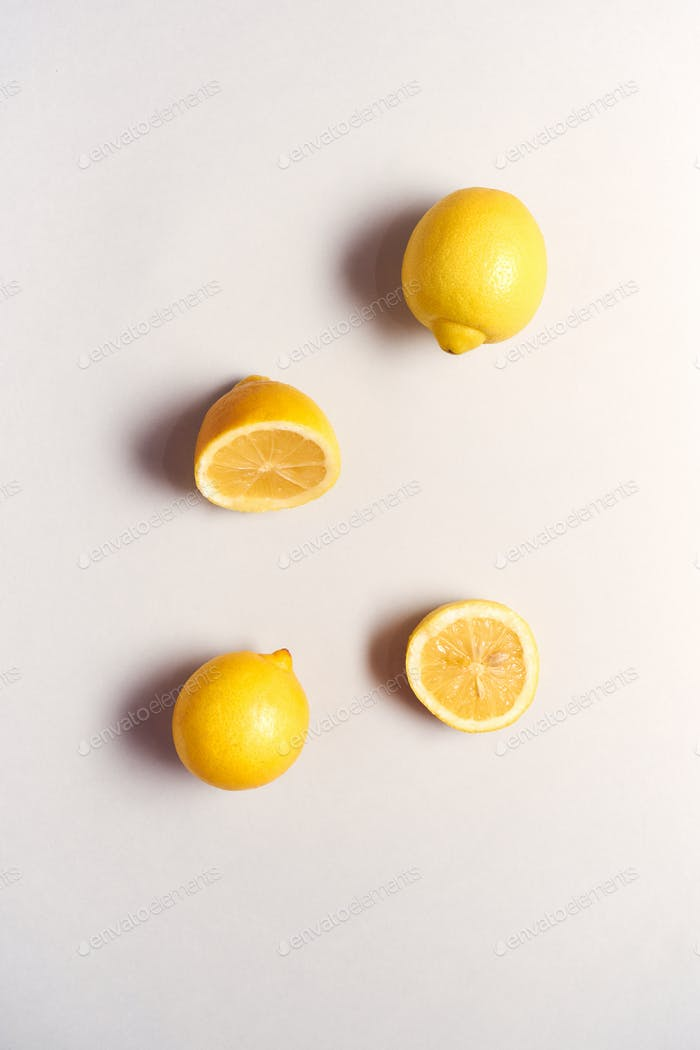 Overhead-Ansicht von Ganze und Halbierte frische Zitronen auf weißem Hintergrund