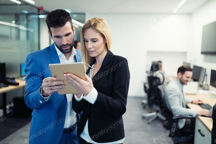 Business colleagues looking at tablet in office
