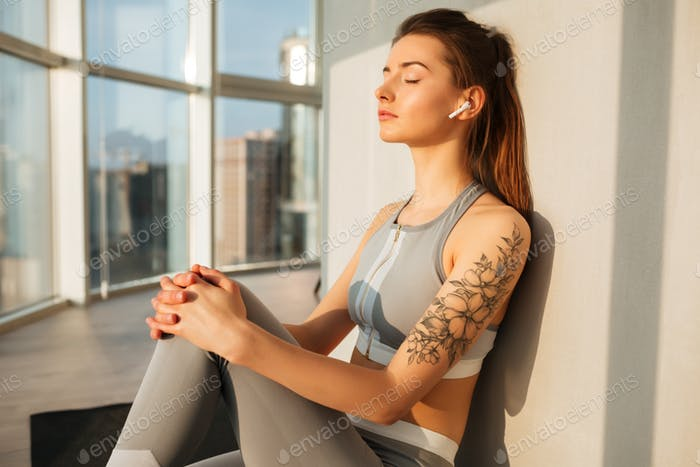 Thoughtful girl sitting on yoga mat listening music in earphones at home over beautiful window