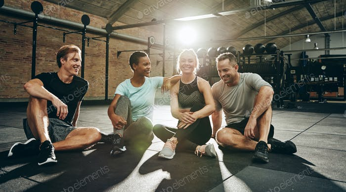 Laughing friends sitting and talking together after a gym workout