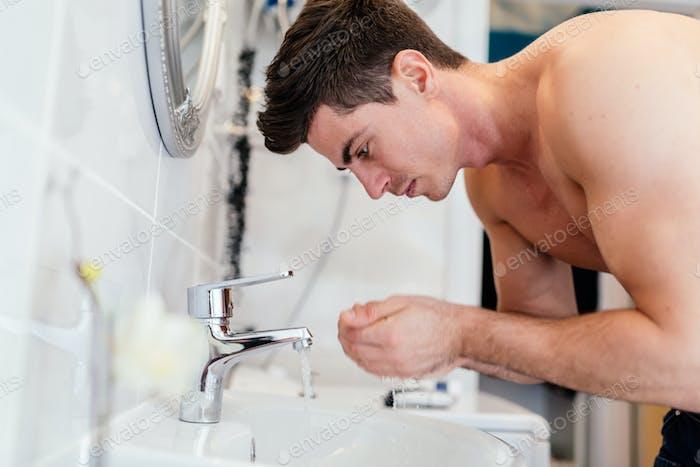 Handsome man washing face in bathroom