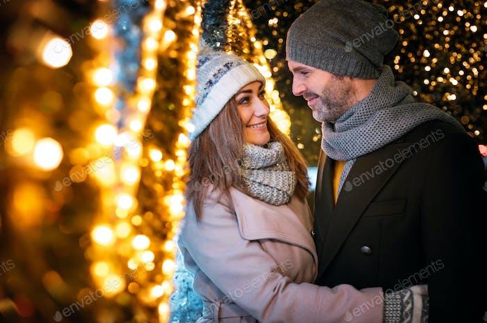 Liebevolle Paar Umarmungen unter Weihnachten Straßendekorationen