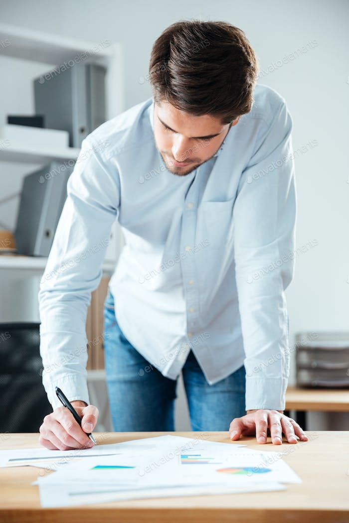 Serious young businessman writing on the table in office