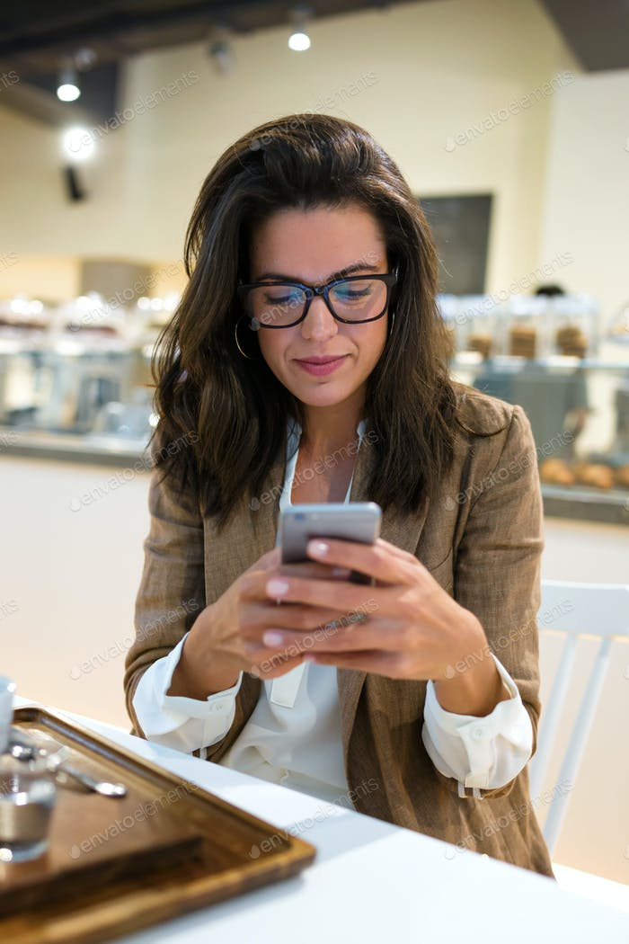 Beautiful young businesswoman with eyeglasses texting with her mobile phone in the coffee shop.
