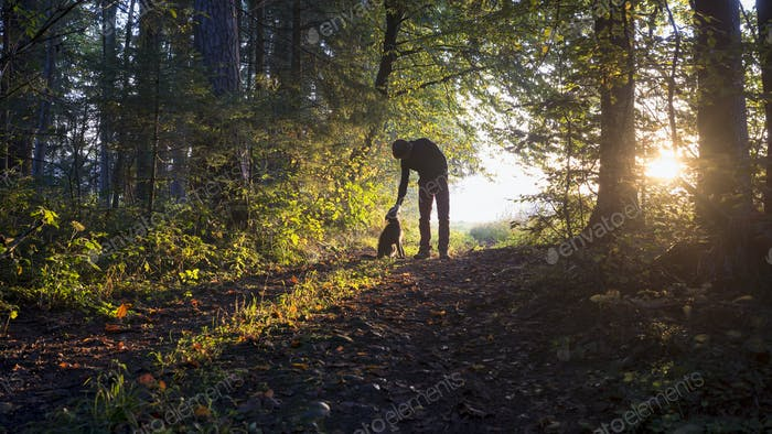 Man bending down to pet his black dog as they enjoy a beautiful nature