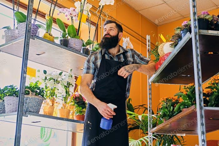 Brutale bärtige Blumenverkäufer mit Tattoos auf seinen Armen in einer Flowe