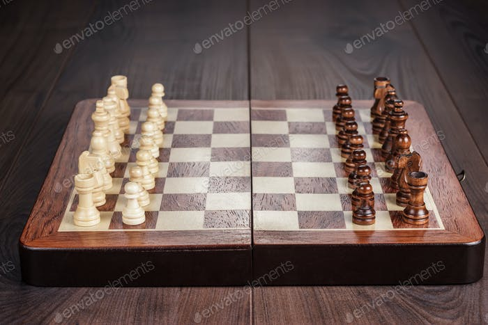 Chess Board With Figures On Wooden Table
