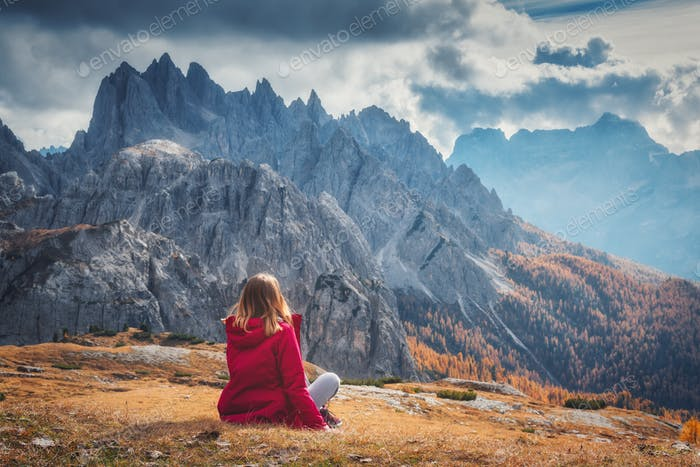 Woman is sitting on the hill against the majestic mountains