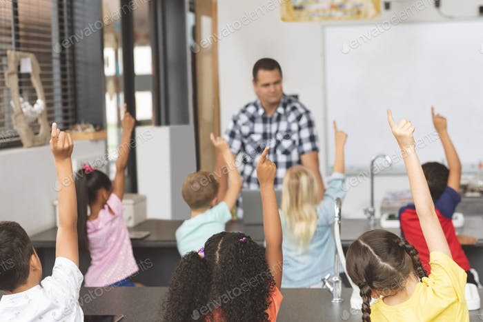 Schoolkids raising hand in classroom to answer at a question of the teacher in background