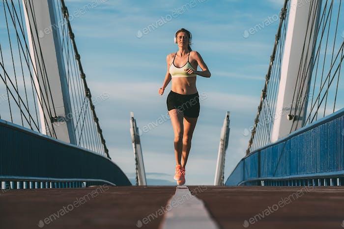 junge fit blonde Frau läuft auf die Brücke