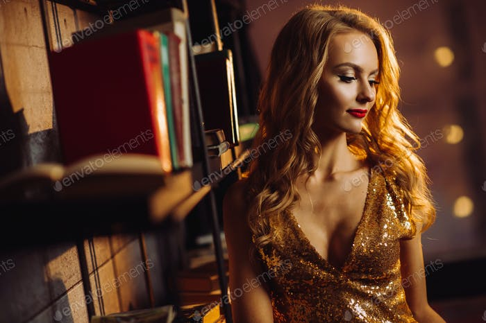 Sexy girl in a gold dress on the background of books in the library.Model with long hair and red