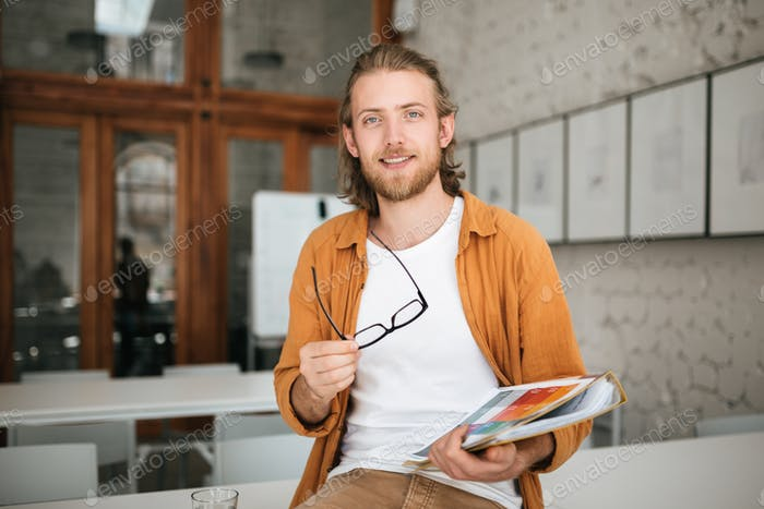 Smiling boy with blond hair and beard joyfully looking in camera holding documents in hand