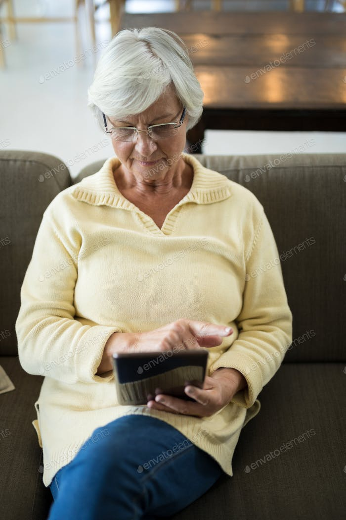 Senior woman using digital tablet on sofa