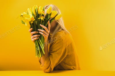 young woman holding beautiful yellow spring flowers on yellow
