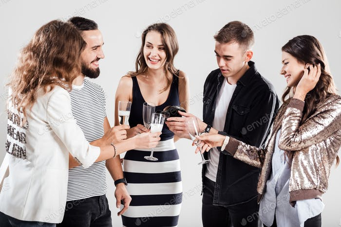 Girls and guys dressed in stylish casual clothes stand together and smile. Guy is pouring champagne