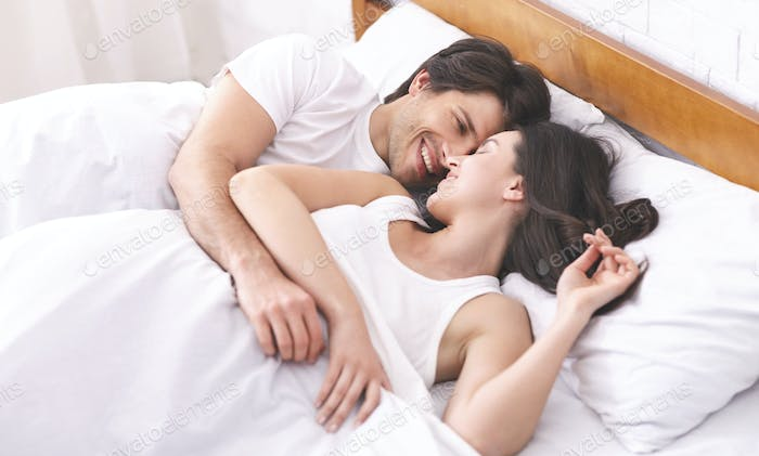 Cheerful millennial man and woman waking up together in bed