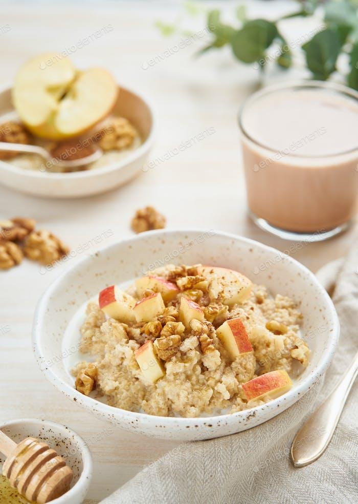 Haferflocken mit Apfel, Nüssen, Zimt, Honig und Tasse Kakao