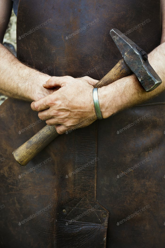 Man in a leather apron holding a hammer.