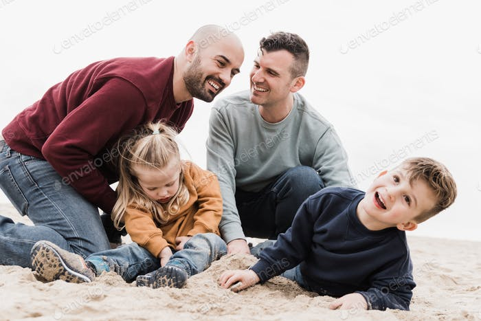 Gay fathers and sons playing on the beach in summer vacation - LGBT family love concept