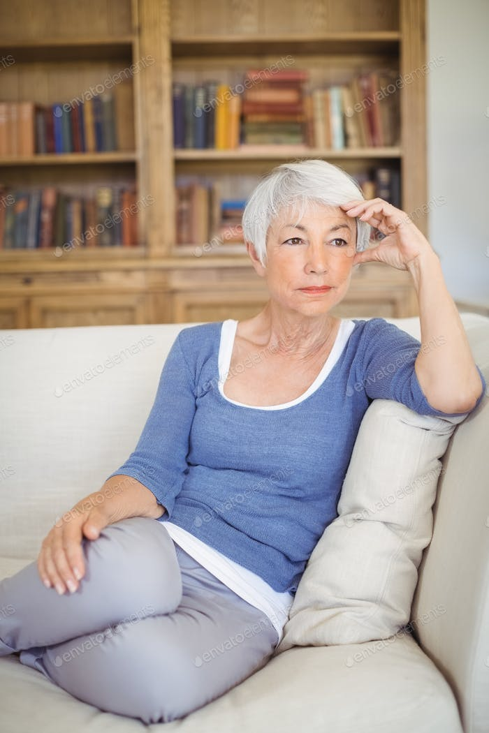 Thoughtful senior woman sitting on sofa in living room