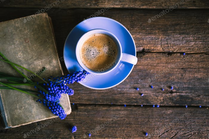 Blue flowers and a cup of coffee with a book on a wooden background