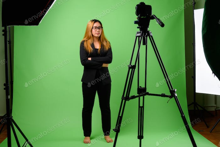 Portrait of young Asian businesswoman against green background