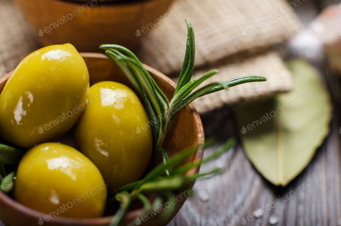 Closeup view of green olives oils and spices on kitchen table. C