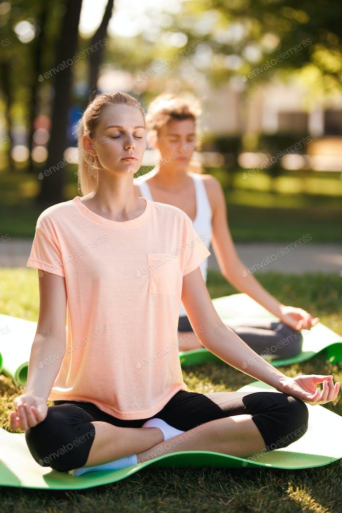 Women doing yoga outdoors at sunrise. Morning meditation