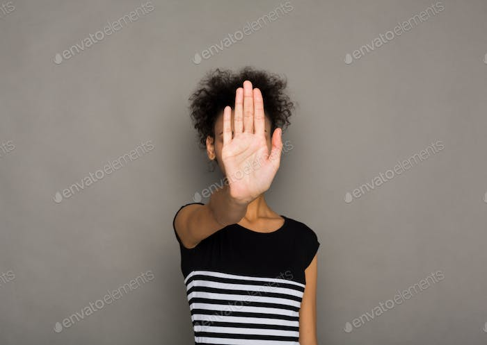 Young woman covering her face with palm