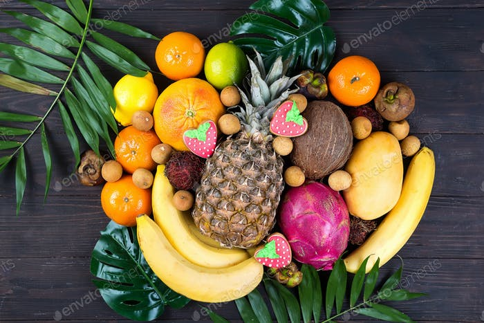 Ripe juicy tropical summer seasonal fruits on palm Leaf on wooden background. Vacation healthy