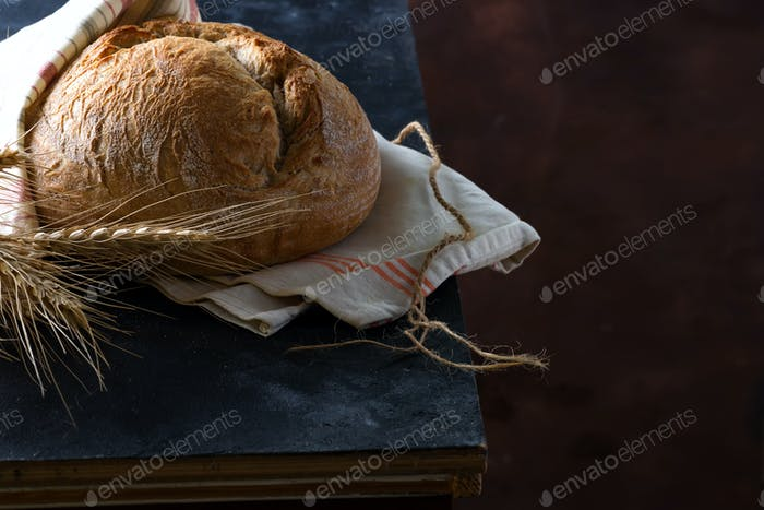 Round freshly baked rustic rye round bread with wheat ears and napkin on a dark background, copy