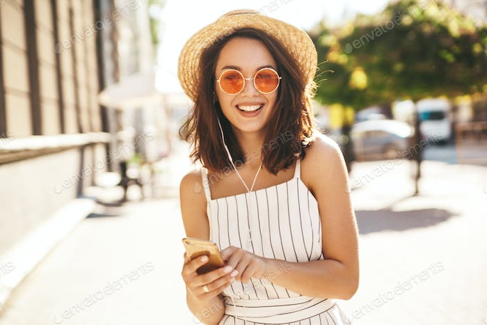 Portrait of beautiful young woman posing outdoors in hat