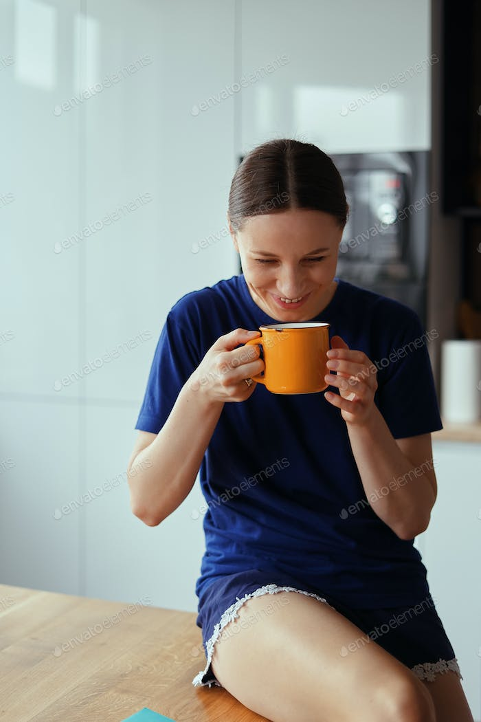 Lovely woman drinking a cup of tea in the kitchen